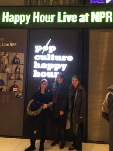 Picture of 3 women in front of a Pop Culture Happy Hour sign
