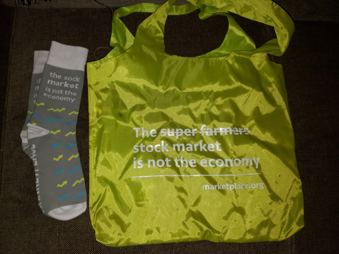 Pair of socks that say the sock market is not the economy and a tote bag that says the super farmer's stock market is not the economy.